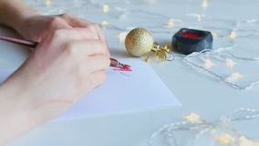 Artistic calligraphy with nib pen and red ink. Hand writing word merry with broad nib pen and red ink. Shimmering yellow garlands on white paper. Concept of stock footage