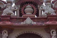 Artistic carving on red and white stone of main gate, bheru tarak dham, rajasthan, I ndia Stock Photography