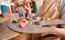 Artistic child using pallet in the art studio. Pallet in my hands. Capable skillful smart kid sitting at school and painting while using paintbrush and pallet Royalty Free Stock Photos