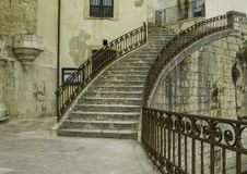 Artistic circular steps with antique decorated metal handrail in old Ragusa Ibla in Sicily royalty free stock photo