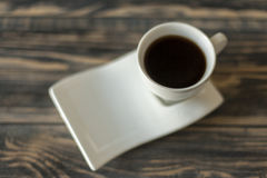 Artistic coffee cup with black coffee on wooden table Royalty Free Stock Photos
