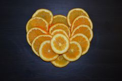 Artistic composition of slices of ripe oranges posed in a shape of a heart on wooden background. royalty free stock photos