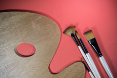 Artistic concept painter`s basic tools - painting concept palette and brushes top view on red background Stock Image