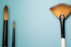 Artistic concept range of paint brushes flat fan round with natural sable hair bristles on blue turquoise background. With copy space royalty free stock image