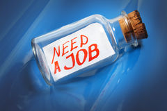 Creative concept of a message in a bottle saying Need a job. An artistic concept of a vintage bottle with a cork and saying Need job floating on blue waves Royalty Free Stock Photography