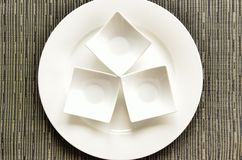 Artistic crockery. Three small bowls on a plate royalty free stock photo
