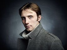 Artistic dark portrait of the young beautiful man in a gray coat. Close up stock image
