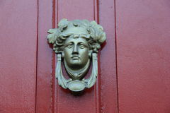 Artistic detail in elaborate knocker on red door of home Stock Photo