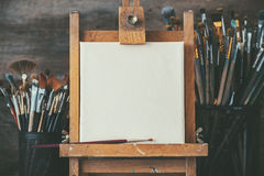 Artistic equipment in a artist studio: empty artist canvas and brushes. Artistic equipment in a artist studio: empty artist canvas on wooden easel and paint Royalty Free Stock Photos