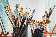 Artistic equipment in studio: painting, easel, paintbrushes and paints. Stock Photo