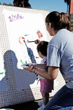 Artistic expression 2. Mother helps her child paint a picture during a street fair Stock Photography