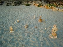 Stacks of stones on the beach sand stock photography