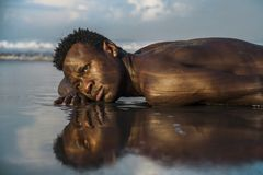 Young attractive and sexy black afro American man with athletic muscular body posing cool in sea water on desert beach in male. Artistic expressive portrait of stock images