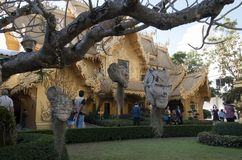 Artistic heads hanging in tree with golden building in background at Wat Rong Khun, Chiang rai by artist Chalermchai Kositpipat stock photos