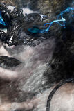 Artistic hieratic and beautiful woman with Venetian mask, blue s. Moke coming out of the eyes, art Royalty Free Stock Photography