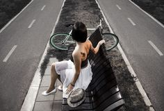 Artistic image, Young tattooed woman sitting on bench Stock Photos
