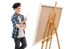 Artistic kid posing next to a canvas Stock Photos