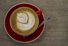 Artistic latte art in a red cup. It is a close up shot of an Artistic latte art in a red cup on a wooden table Royalty Free Stock Photography