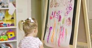 Artistic little girl painting a creative design stock video footage