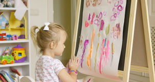 Artistic little girl painting a creative design Stock Photo