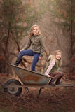 Artistic outdoor portrait of two blond girls playing with a wheel barrow in a woods Stock Images