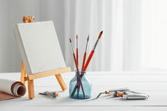 Artistic paintbrushes, canvas on easel and tubes of paint Royalty Free Stock Photography