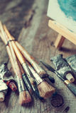 Artistic paintbrushes, tubes of oil paint, palette knife and easel with oil painting. stock image