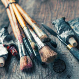 Artistic paintbrushes, tubes of oil paint, palette knife on old. Wooden desk. Vintage stylized Royalty Free Stock Photos