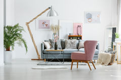Artistic paintings in living room. Beige blanket in basket on floor in living room with pink armchair and artistic posters on wall royalty free stock photo