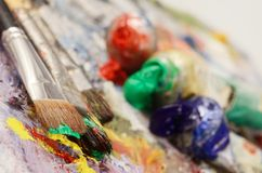 Artistic palette with colourful oil paints, creative background. Artistic palette with colourful oil paints, dirty brushes - background for creative art design royalty free stock photo