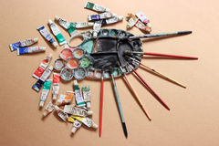 Artistic pallette with oils, paint brushes, tubes. Used artistic palette with oils, paint brushes and tubes on paper canvas Stock Photo