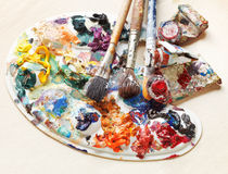 Artistic pallette with oils, paint brushes, tubes Stock Images
