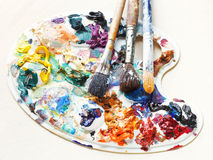 Artistic pallette with oils and paint brushes Royalty Free Stock Images
