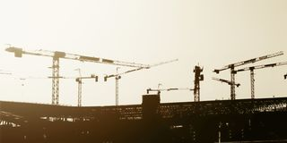 Artistic panorama view silhouette group of tower cranes working on construction site. royalty free stock photography