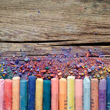 Artistic pastel crayons and pigment dust on rustic wooden backgr Royalty Free Stock Photos
