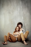 Artistic portrait of a young couple on a gray. Textural background Royalty Free Stock Photo