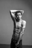 Artistic portraits of young topless man on gray background royalty free stock photography