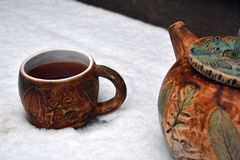 A teapot and a cup of tea in the first snow royalty free stock image