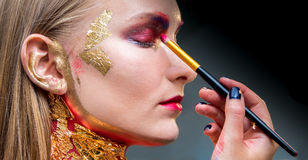 Artistic professional make up applies eye shadow. Beautiful woman face Royalty Free Stock Photography