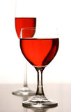 Artistic red. Two glasses of red concoction in glasses against white background lighting Royalty Free Stock Photos
