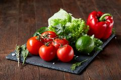 Artistic still life of assorted fresh vegetables and herbs on rustic wooden background, top view, selective focus. Artistic seasoning close-up still life of Stock Photos