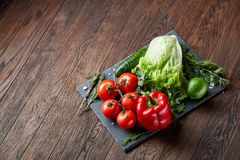Artistic still life of assorted fresh vegetables and herbs on rustic wooden background, top view, selective focus. Artistic seasoning close-up still life of Royalty Free Stock Photography