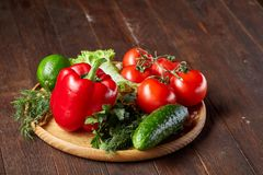 Artistic still life of assorted fresh vegetables and herbs on rustic wooden background, top view, selective focus. Artistic seasoning close-up still life of Royalty Free Stock Photo