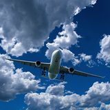 Airliner in flight with Cumulus cloud in blue sky. Australia. An artistic skyscape view of a commercial passenger jet aircraft flyng in a vibrant blue sky, with stock photos