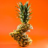 Artistic sliced, standing pineapple on orange background, square shot Stock Photo