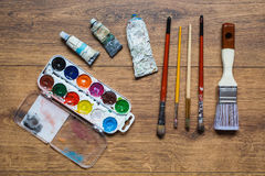 Artistic squirrel brushes, tubes of oil paints and watercolors on a wooden background. Used tools for artists, students and schoolchildren. Stained with paint Stock Image