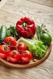 Artistic still life of assorted fresh vegetables and herbs on rustic wooden background, top view, selective focus. Artistic seasoning close-up still life of Stock Photography