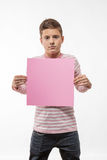 The artistic teenager boy brunette in a pink jumper with a pink sheet of paper for notes Royalty Free Stock Images