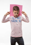 The artistic teenager boy brunette in a pink jumper with a pink sheet of paper for notes. On a white background Royalty Free Stock Photography