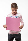 The artistic teenager boy brunette in a pink jumper with a pink sheet of paper for notes. On a white background Stock Photos
